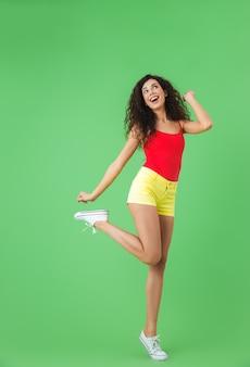 Pełna długość portret radosnej dziewczyny ubranej w letnie ubrania, uśmiechniętej i chodzącej na białym tle nad zieloną ścianą
