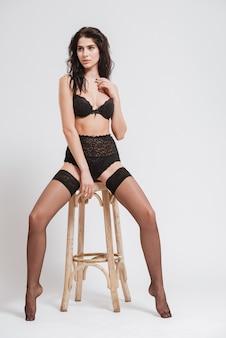 Pełna długość portret seksownej brunetki w czarnej bieliźnie z pończochami pozowanie na krześle na białym tle