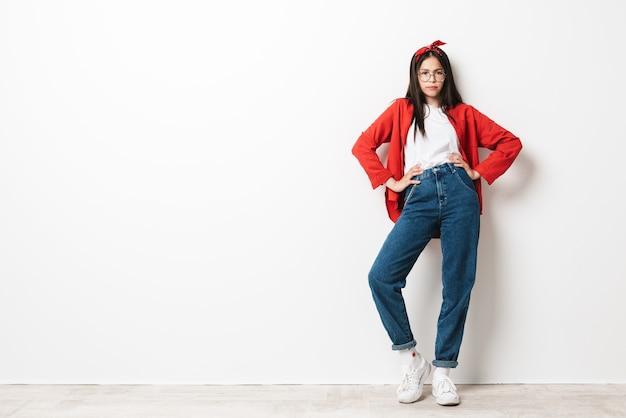 Pełna długość portret słodkiej zdenerwowanej nastolatki w swobodnym stroju stojącej na białym tle nad białą ścianą, ramiona na biodrach