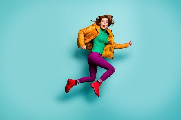 Pełna długość portret śmiesznej szybkiej pani skaczącej w pośpiechu sprzedaż centrum handlowego fajne ceny nosić żółty płaszcz szalik magenta spodnie golf czerwone buty.
