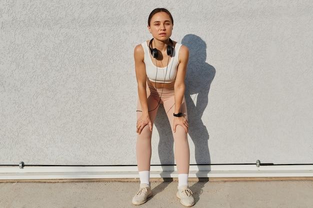 Pełna długość portret sportowa szczupła kobieta ubrana w biały top i beżowe legginsy, ze słuchawkami na szyi, opierając się na ścianie na świeżym powietrzu, pozowanie po treningu.