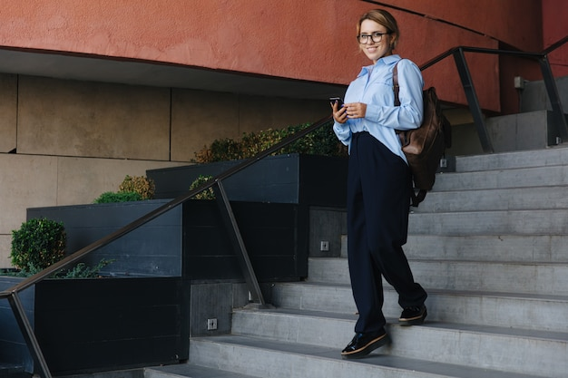 Pełna długość portret studentki w dorywczo strój stojący na schodach i trzymając smartfon. młoda kobieta spędza czas wolny z gadżetem na ulicy z plecakiem.