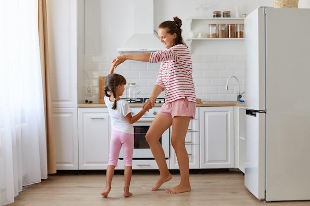 Pełna długość portret szczęśliwa optymistyczna matka i córka razem tańczą przeciwko zestawowi kuchennemu w domu, ubrany niedbale, wyrażając szczęście, dzieciństwo.