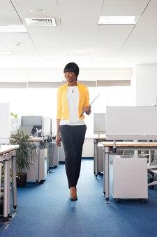 Pełna długość portret szczęśliwej kobiety chodzącej w biurze