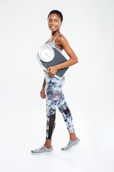 Pełna długość portret szczęśliwej kobiety fitness trzymającej maszynę do ważenia na białej ścianie