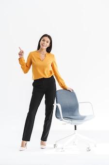 Pełna długość portret szczęśliwej młodej bizneswoman ubranej w elegancki strój, wskazując palcami na copyspace i stojąc przy krześle na białym tle nad białą ścianą