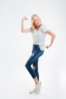 Pełna długość portret szczęśliwej młodej kobiety pokazującej jej mięśnie odizolowane na białej ścianie