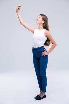 Pełna długość portret szczęśliwej nastolatka robi zdjęcie selfie na smartfonie na białym tle