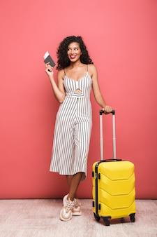 Pełna długość portret szczęśliwej pięknej młodej kobiety w letniej odzieży stojącej z walizką odizolowaną nad różową ścianą, trzymającej paszport z biletami lotniczymi