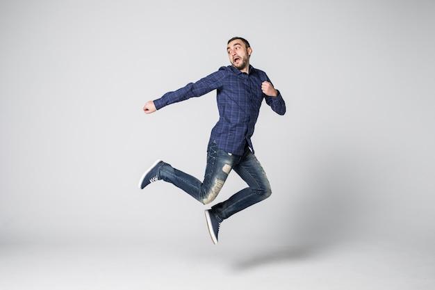 Pełna długość portret szczęśliwy podekscytowany brodaty mężczyzna skoki i patrząc na kamery na białym tle nad białym tle