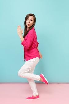 Pełna długość portret uśmiechnięta młoda ładna kobieta w różowej bluzce koszulowej, białe spodnie pozowanie na białym tle na jasny różowy niebieski pastelowy mur.