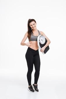 Pełna długość portret uśmiechniętej ładnej sportowej kobiety stojącej i wskazującej palcem na wagę na białym tle