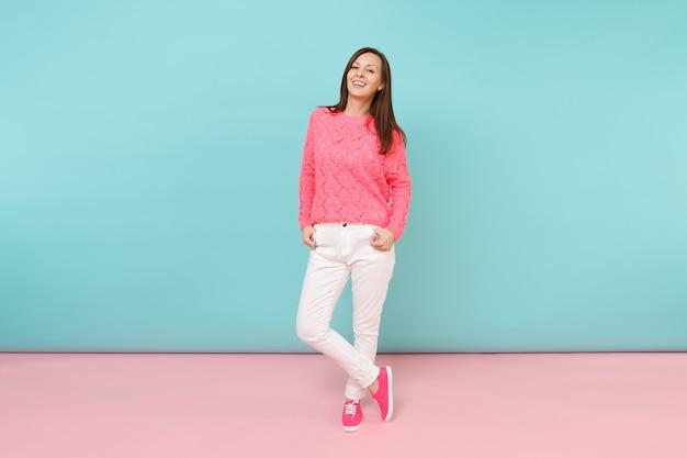 Pełna długość portret uśmiechniętej młodej kobiety w dzianinowym swetrze z różami, pozowanie białe spodnie