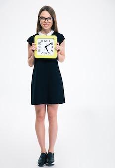 Pełna długość portret uśmiechniętej studentki trzymającej duży zegar na białym tle