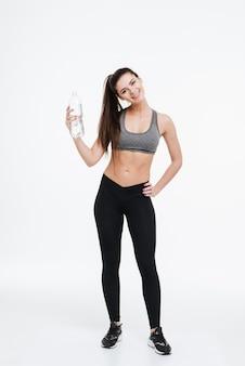 Pełna długość portret uśmiechniętej wesołej kobiety fitness stojącej i trzymającej butelkę wody na białym tle