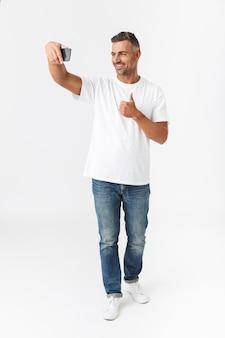 Pełna długość portret uśmiechnięty mężczyzna 30s ubrany w casual t-shirt i dżinsy biorąc selfie zdjęcie na telefonie komórkowym, trzymając w ręku na białym tle