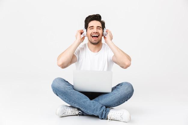 Pełna długość portret wesołego młodego mężczyzny noszącego zwykłą odzież na białym tle nad białym, siedzącego z laptopem, noszącego słuchawki