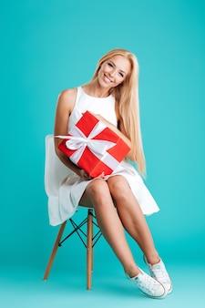 Pełna długość portret wesołej blondynki kobiety trzymającej pudełko i siedzącej na krześle na białym tle na niebieskim tle
