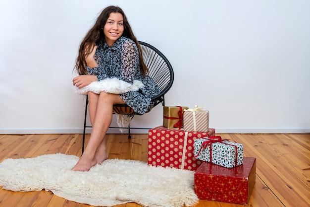 Pełna długość portret wesołej brunetki siedzącej na krześle w pobliżu stosu pudełek na prezenty, miejsce kopiowania