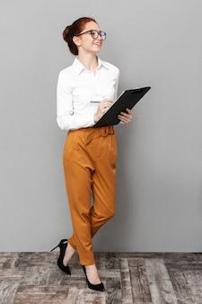 Pełna długość portret wesołej rudej bizneswoman 20s w okularach, trzymając schowek i uśmiechając się w biurze na białym tle nad szarym