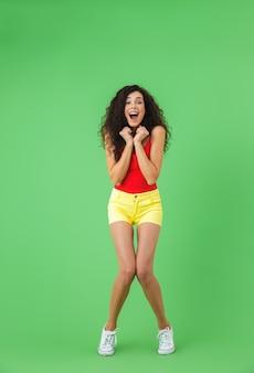 Pełna długość portret wysportowanej dziewczyny ubranej w letnie ubrania, uśmiechniętej i chodzącej na białym tle nad zieloną ścianą