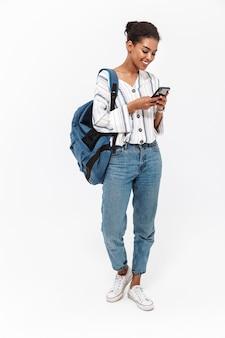 Pełna długość portretu atrakcyjnej młodej afrykańskiej kobiety niosącej plecak stojący na białym tle nad białą ścianą, przy użyciu telefonu komórkowego