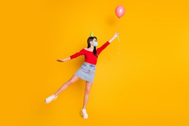 Pełna długość profil strona zdjęcie dziewczyna maska medyczna mieć covid rocznicę uroczystości złapać powietrze latać balon nosić czerwony top denim dżinsy dorywczo spódnica nogi na białym tle jasny połysk kolor tła