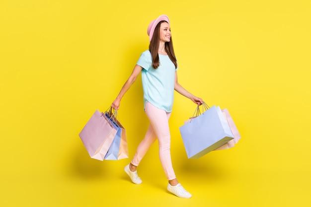Pełna długość profil strona zdjęcie pozytywne dziewczyna turysta odpoczynek relaks kup prezenty trzymaj torby idź spacer centrum handlowe copyspace nosić niebieski t-shirt różowe spodnie spodnie nakrycia głowy na białym tle jasny połysk kolor tła