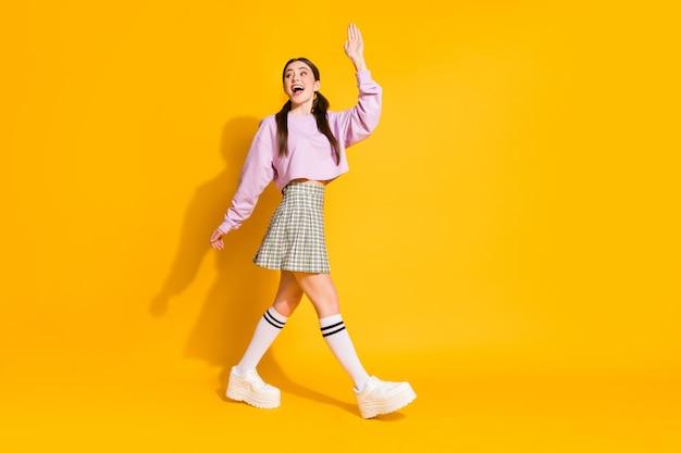 Pełna długość profilu podekscytowanej energicznej nastolatki idzie na spacer pożegnać się
