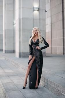 Pełna długość przepięknej szczupłej blondynki z długimi falującymi włosami i dużym biustem pozuje na ulicy w błyszczącej czarnej sukience i szpilkach.