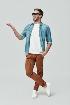 Pełna długość przystojnego młodego mężczyzny wskazującego miejsce na kopię i uśmiechającego się, stojąc na szarym tle
