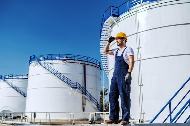 Pełna długość przystojnego pracownika rasy kaukaskiej w kombinezonie i hełmie na głowie stojącego na zewnątrz. produkcja oleju. w tle zbiorniki z ropą.