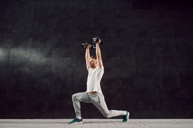 Pełna długość przystojny sprawny mięśni kaukaski blond brodaty mężczyzna w dres i t-shirt robi rzuca się z hantlami w ręce.
