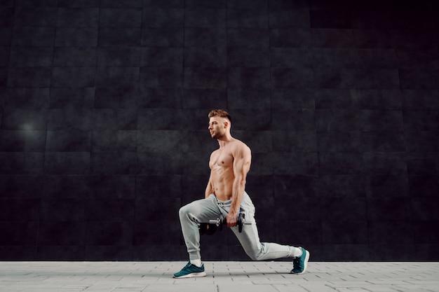 Pełna długość przystojny sprawny mięśni kaukaski półnagi blond brodaty mężczyzna w dresie robi rzuca się z hantlami w ręce.