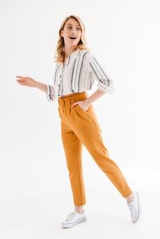 Pełna długość radosna młoda kobieta nosząca zwykłe ubrania, patrząca na bok i spacerująca na białym tle nad białą ścianą