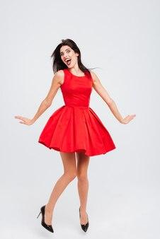 Pełna długość radosnej słodkiej młodej kobiety w czerwonej sukience tańczącej i bawiącej się na białym tle
