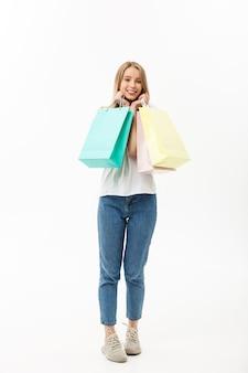Pełna długość shopper kobiety trzymającej torby na zakupy stojący szczęśliwy uśmiechnięty i podekscytowany w całym ciele na białym tle.