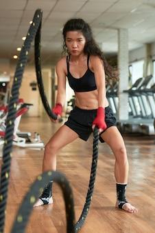 Pełna długość sportsmenki wykonywania ćwiczeń liny bitwy
