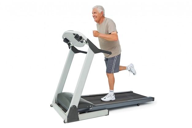Pełna długość starszy człowiek działa na bieżni