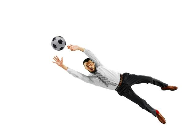 Pełna długość strzał młodego biznesmena gry w piłkę nożną na białym tle na białej ścianie