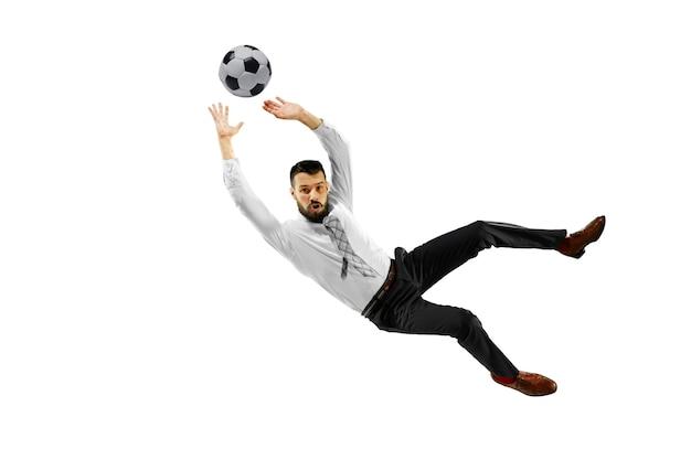 Pełna długość strzał młodego biznesmena gry w piłkę nożną na białym tle.