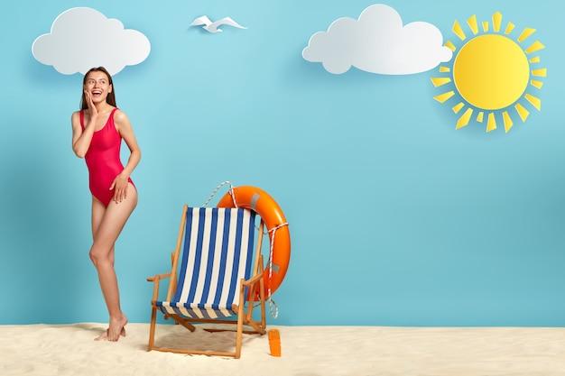 Pełna długość strzał szczęśliwej kobiety spoczywa na tropikalnej plaży