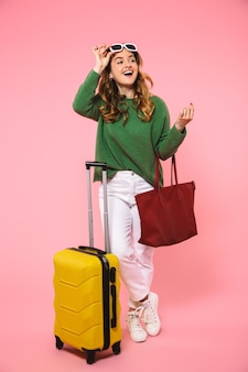 Pełna długość szczęśliwa blondynka ubrana w zielony sweter i okulary przeciwsłoneczne pozuje z bagażem i odwraca wzrok na różowej ścianie