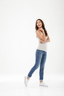 Pełna długość szczęśliwa brunetki kobieta pozuje z powrotem i patrzeje nad popielatym