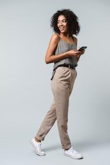 Pełna długość szczęśliwa młoda afrykańska kobieta ubrana niedbale stojąc na białym tle, trzymając telefon komórkowy