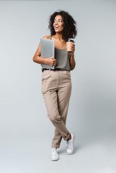 Pełna długość szczęśliwa młoda afrykańska kobieta ubrana niedbale, stojąca na białym tle, niosąca laptop, trzymając kubek na wynos