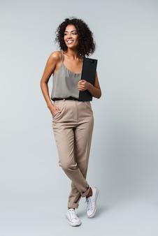 Pełna długość szczęśliwa młoda afrykańska kobieta ubrana niedbale, stojąca na białym tle, trzymając notatnik