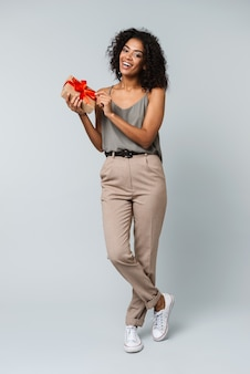 Pełna długość szczęśliwa młoda afrykańska kobieta ubrana niedbale, stojąca na białym tle, trzymając pudełko