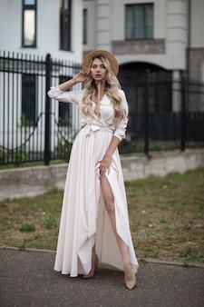 Pełna długość szczęśliwa piękna młoda kobieta ubrana w sukienkę i chodząca po ulicy, stojąc w pobliżu ogrodzenia. koncepcja piękna i mody