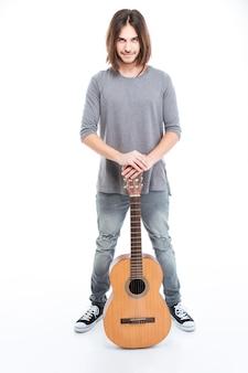 Pełna długość szczęśliwego pewnego siebie młodego człowieka stojącego z gitarą na białym tle